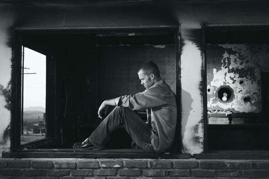 anxiety and depression | b&w photo of a sad man sitting in a window | Dr. Negin Misaghi, ND